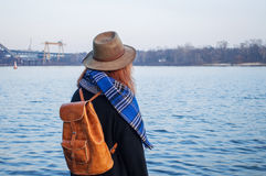 Young woman in hat and with rucksack standing on the riverbank, looking at sunset or sunrise horizon, back view Royalty Free Stock Images