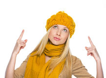 Young woman in hat and scarf pointing up on copy space Stock Photos