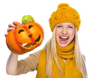 Young woman in hat and scarf scaring with jack-o-lantern. High-resolution photo Stock Images