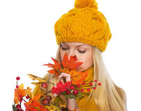 Young woman in hat and scarf smelling autumn bouquet Stock Photo