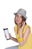 The young woman in a hat sits with coffee and phone Royalty Free Stock Photography