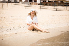 Young woman in hat sitting on beach and using digital tablet Stock Photos