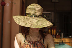 Young woman with hat sitting in a cafe in the summer Stock Photos