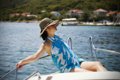 Young woman with hat sitting on the front of a sail boat Royalty Free Stock Photos