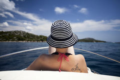 Young woman with hat sitting on the front of a sail boat Stock Photo