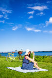 Young woman in hat sitting on the sea coast with vintage bicycle Stock Image