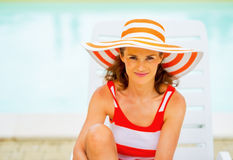 Young woman in hat sitting on sunbed Stock Photo