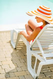 Young woman in hat sitting on sunbed. rear view Stock Photo