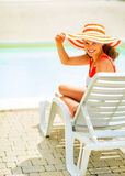 Young woman in hat sitting on sunbed Stock Photos