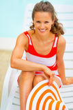 Young woman with hat sitting on sunbed Royalty Free Stock Images