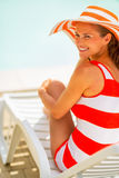 Young woman in hat sitting on sunbed Royalty Free Stock Images