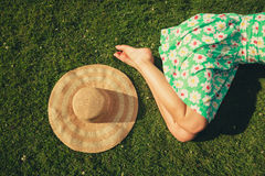 Young woman with hat sleeping in the park. A young woman wearing a dress is sleeping on the grass with a hat next to her Stock Photo