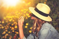 Young woman in hat smells poppy in nature. Vintage style Stock Images