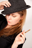 Young woman with hat is smoking a cigar Royalty Free Stock Photos
