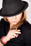 Young woman with hat is smoking a cigar Stock Images
