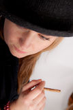 Young woman with hat is smoking a cigar Stock Photo