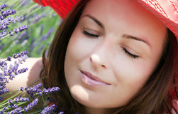 Young woman with hat sniffs lavender flowers Royalty Free Stock Images