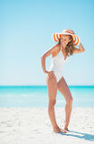 Young woman in hat standing on beach Royalty Free Stock Photos