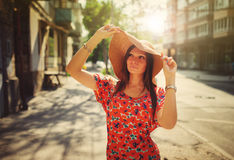 Young woman in hat standing on street Stock Photos