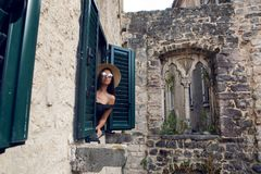 Young woman in hat and sunglasses looks out from the window. Of the old stone buildings Royalty Free Stock Images