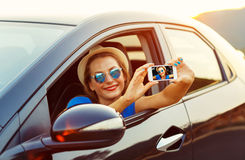 Young woman in hat and sunglasses making self portrait sitting i royalty free stock photography