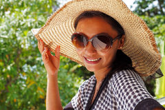 Young woman in a hat and sunglasses standing on a balcony Royalty Free Stock Image
