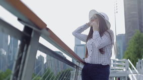 A young woman in a hat and sunglasses is standing under sun on promenade and talking on phone. stock footage