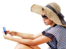 Young woman in a hat and sunglasses using her mobile phone Stock Images