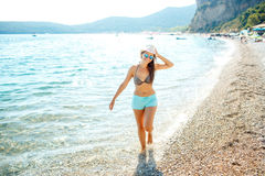 Young woman in a hat and swimsuit walking on the beach on a hot Royalty Free Stock Photo