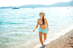 Young woman in a hat and swimsuit walking on the beach on a hot Royalty Free Stock Photography