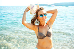 Young woman in a hat and swimsuit walking on the beach on a hot Royalty Free Stock Images