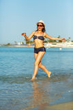 Young woman in a hat and swimsuit walking on the beach on a hot Royalty Free Stock Image