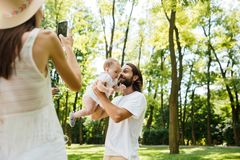 Young woman in a hat takes a photo of her husband holding in the arms their little charming daughter on a sunny day in stock photography