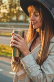 Young woman in a hat with thermos thermo cup outdoor portrait in soft sunny daylight. Autumn. Sunset. Cozy stock images