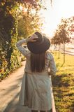 Young woman in a hat with thermos thermo cup outdoor portrait in soft sunny daylight. Autumn. Sunset. Cozy stock photos