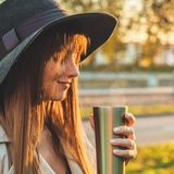 Young woman in a hat with thermos thermo cup outdoor portrait in soft sunny daylight. Autumn. Sunset. Cozy stock image