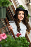 Young woman with hat in urban background wearing casual clothes. Portrait of young woman smiling in urban background wearing casual clothes and hat Royalty Free Stock Images