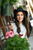 Young woman with hat in urban background wearing casual clothes. Portrait of young woman smiling in urban background wearing casual clothes and hat Royalty Free Stock Photography