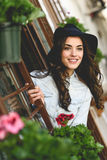 Young woman with hat in urban background wearing casual clothes. Portrait of young woman smiling in urban background wearing casual clothes and hat Stock Image