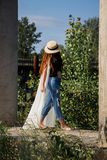 Young woman in the hat walking in the park royalty free stock image