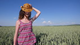 Young woman in a hat walking on a wheat field with blue sky on the background stock footage