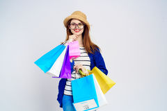 A young woman in a hat and wearing glasses keeps a lot of packages.  Royalty Free Stock Image