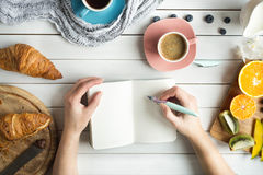 Young woman have a breakfast with fresh croissants, coffee and fruits and her hands drawing or writing with ink pen. In open notebook on white wooden table. Top stock photo