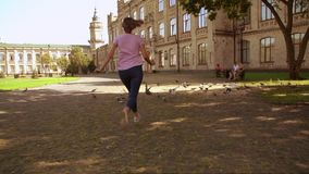 Tourist spend time at the open air. Young woman have fun in city. funny girl running past pigeons. on the background beautiful old building stock footage