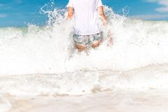 Young woman haveing fun with ocean waves on a tropical beach of Bali island, Indonesia. Rare view. Young woman haveing fun with ocean waves on a tropical beach Royalty Free Stock Image