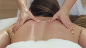 Young woman having anti cellulite back massage in beauty spa salon. Masseuse makes cellulite massage to a young. Beautiful girl on the background of a candle stock footage