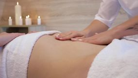 Young woman having anti-cellulite belly massage in a beauty spa salon. A masseuse makes cellulite massage of a young. Beautiful girl on the background of a stock video footage