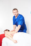 Young woman having back massage. The young women having back massage in spa salon Stock Images