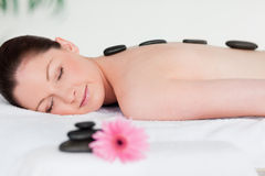 Young woman having a black stones massage Stock Photos