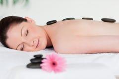 Young woman having a black stones massage Stock Photos